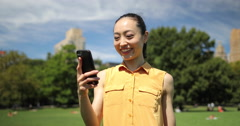 Asian woman in city park taking selfie photo on cell phone video chat Stock Footage