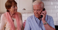 4k, You have a call.. Old couple receive a phone call on their mobile phone. Stock Footage
