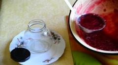 Woman puts handmade raspberry jam in jar Stock Footage