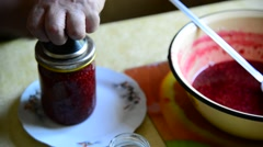 Woman closes a lid of handmade raspberry jam in jar Stock Footage
