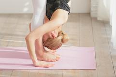 Attractive young Japanese practicing yoga in an airy room Stock Photos