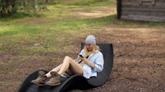 Girl With a Phone Resting on a Lounger in a Forest Glade Stock Footage