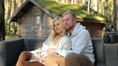 Young Couple Hugging Sitting on the Sofa at the Cabin in the Woods Stock Footage