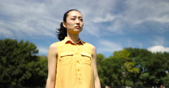Asian woman in city park walking sad face depressed slow motion Stock Footage