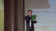 The young man with plate reads the text on the stage Stock Footage