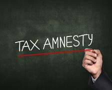 Hand holding pen and write tax amnesty words Stock Photos