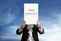 The human holding paper reads tax amnesty Stock Photos