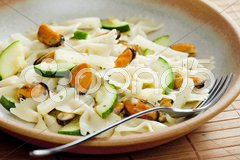 Pasta farfalle with mussels and zucchini Stock Photos