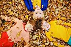 Three Kids Lying in Fallen Leaves Stock Photos