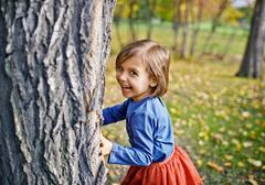 Girl Playing Hide and Seek in Park Stock Photos