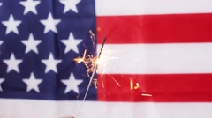 Close up of sparkler burning over american flag Stock Footage