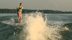 Wakeboarder girl jump the waves on lake water, summer sunset Stock Footage
