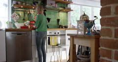 Girl aking a cake in the kitchen with a cat as company on the bench Stock Footage