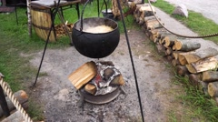 Cooking In A Hike In The Cauldron Hanging Over fire Stock Footage