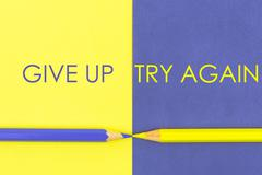 Give Up versus Try Again contrast concept Stock Photos