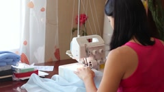 Beautiful woman sews. Powered by overlock. View from the back. Work is fun Stock Footage