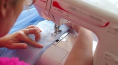 Woman sews on the sewing machine. Women's hands. from behind. Close-up Stock Footage