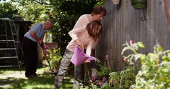 4k, Happy little girl with her grand parents gardening on a bright sunny day. Stock Footage