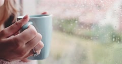 Young Woman Enjoying Coffee Looking Out the Rainy Window. 4K SLOW MOTION. Stock Footage