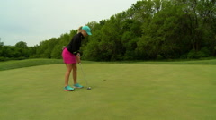 A young woman with nice legs steps up to the ball on the putting green and putts Stock Footage