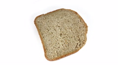 Slice of  homebaked bread rotating at white background Stock Footage