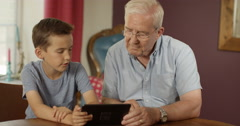 4k, Grand father and a little boy using a digital touchscreen tablet. Stock Footage