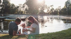 Young family with Baby Girl Enjoying evening in Park. Slow Motion 120 fps 4K Stock Footage
