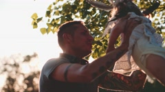 Young Father with Baby Girl Enjoying Sunny evening outdoors. Slow Motion 120 Stock Footage