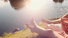 Family with Toddler Girl on Grass by the lake, close up on feet. Slow Motion 4K Stock Footage