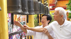 Asian senior couple doing ritual bell ringing in Buddhist temple Stock Footage
