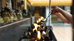 Asian senior doing Buddhist ritual pouring oil to fill candle flame Stock Footage