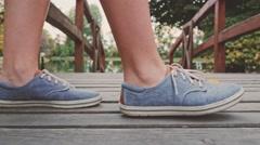 Woman Feet wearing Sneakers Shoes crossing Wooden Bridge in Autumn Park. 4K. Stock Footage