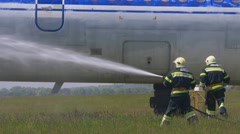 Team of fire fighters hold a hose and water jet extinguishes during a simulated Stock Footage