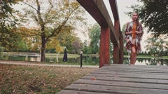Woman wearing Denim Sneakers Shoes crossing Wooden Bridge in Autumn Park. 4K. Stock Footage