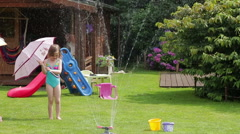 Little girl playing with garden sprinkler and umbrella, slow motion HD Stock Footage