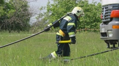 Firefighters pulling down fire hose during a training at Boryspil International Stock Footage