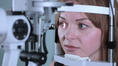 Young woman having her eyes examined with modern medical equipment Stock Footage