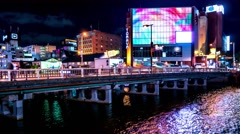 Fukuoka -  Night view of glowing city by the river with traffic on the bridge. Stock Footage