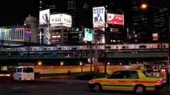 Tokyo - Night street view with glowing signboards trains and traffic at Shinjuku Stock Footage