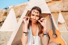 Amusing woman making funny face in wigwam on the beach Stock Photos