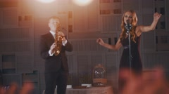 Jazz vocalist in black dress perform on stage at microphone with saxophonist Stock Footage