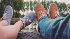 POV: Couple on a wooden jetty playing footsie, close up on hipster shoes. 4K Stock Footage