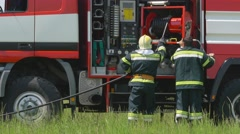 Firefighters pulling down fire hose into fire engine during a training at Stock Footage