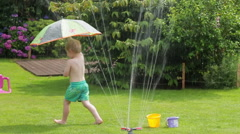 Little boy playing with garden sprinkler and umbrella HD Stock Footage