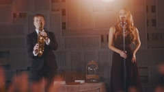 Attractive jazz vocalist in black dress perform dance on stage with saxophonist Stock Footage