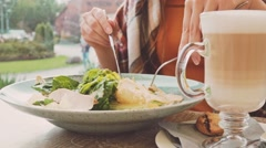 Healthy Woman eating salad in an outdoor cafe. Slow Motion 120 fps. Dolly shot. Stock Footage