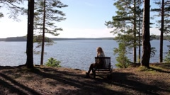 Woman Relaxing on a Lounger on a Cliff Forest Lake Stock Footage