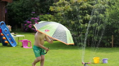 Little boy playing with garden sprinkler and umbrella, slow motion HD Stock Footage