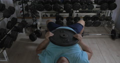 Grown man in a gym lying on bench and raises damn over head Stock Footage