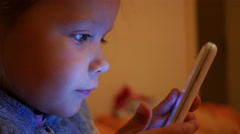 Little child girl typing sliding watch cartoons via smart phone display at night Stock Footage
